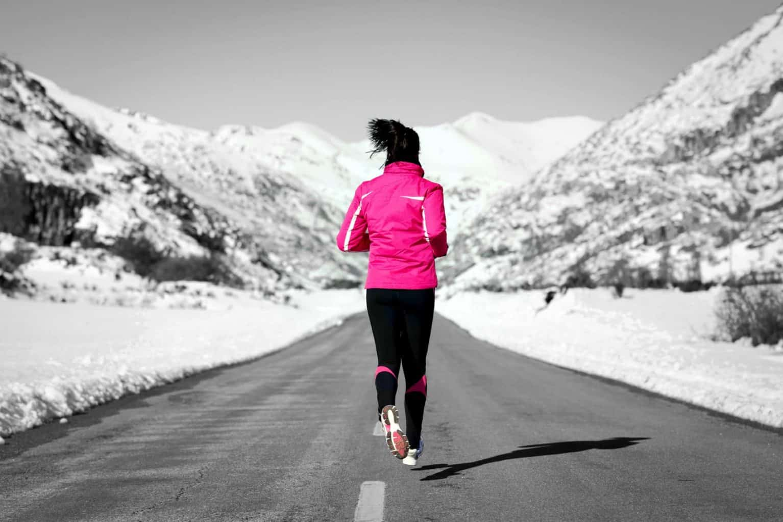 Woman running in cross country road on winter. Rear view of female runner training for marathon in snowy mountains landscape.